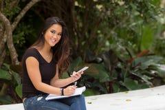 Weiblicher asiatischer Student, der außerhalb des Schreibens in der Notizbuchzeitschrift sitzt Stockbilder