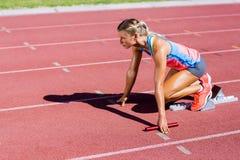 Weiblicher Athlet bereit, den Staffellauf zu beginnen lizenzfreies stockbild