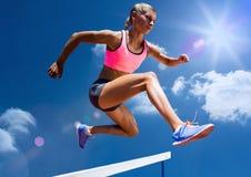 Weiblicher Athlet, der über die Hürde springt lizenzfreies stockfoto