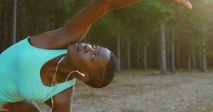 Weiblicher Athlet, der Übung ausdehnend während hörende Musik im Wald 4k durchführt stock video footage