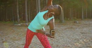 Weiblicher Athlet, der Übung ausdehnend während hörende Musik im Wald 4k durchführt stock footage