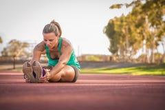 Weiblicher Athlet, der auf eine Laufbahn ausdehnt Stockfotografie