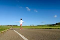Weiblicher Athlet, der auf Straße läuft Lizenzfreie Stockfotografie