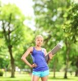 Weiblicher Athlet, der eine trainierende Matte im Park hält Stockbild