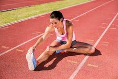 Weiblicher Athlet, der ihre Kniesehne ausdehnt Stockfotos