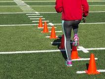 Weiblicher Athlet, der laufende Bohrgeräte über Kegeln durchführt stockfotos