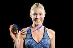 Weiblicher Athlet, der mit Goldmedaille um seinen Hals aufwirft Stockbild