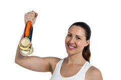 Weiblicher Athlet, der mit Goldmedaillen nach Sieg aufwirft Stockfoto
