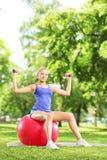 Weiblicher Athlet in einem Park, der auf einem Ball sitzt und mit d trainiert Lizenzfreie Stockfotos