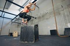 Weiblicher Athlet führt Kastensprünge an der Turnhalle durch Stockbilder