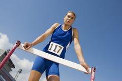 Weiblicher Athlet Standing At Hurdle Lizenzfreie Stockbilder