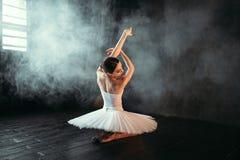Weiblicher Ausführender des klassischen Balletts, der auf Boden sitzt stockfotos