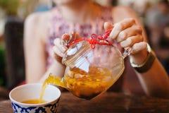 Weiblicher auslaufender Sanddorn-Tee Hnds im Glaskessel stockbilder
