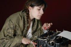 Weiblicher Autor, der auf einer alten Schreibmaschine schreibt Lizenzfreie Stockfotos
