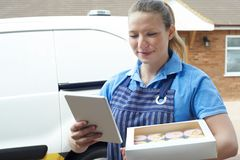 Weiblicher Bäcker With Digital Tablet, das Hauslieferung vom kleinen Kuchen macht Stockbilder