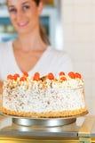 Weiblicher Bäcker- oder Gebäckchef mit torte Stockfotos