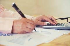 Weiblicher Büroangestellter, der auf der Tastatur schreibt und ein calculat verwendet Stockfoto
