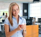 Weiblicher Büroangestellter, der Mobiltelefon verwendet Stockfoto