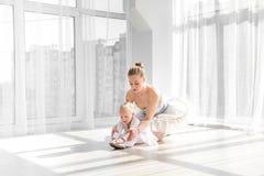 Weiblicher Balletttänzer, der das kleine Mädchen tut exarcises für das Ausdehnen unterrichtet stockbilder