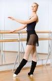 Weiblicher Balletttänzer, der nahe Barre in der Tanzenhalle tanzt Lizenzfreies Stockbild