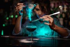Weiblicher Barmixer, der auf das braune Cocktail und auf ein geflammtes badian auf Pinzette ein Puderzucker im grünen Licht gießt stockbild