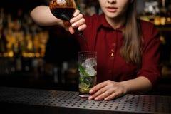 Weiblicher Barmixer, der einen Alkohol dem Cocktail hinzufügt Lizenzfreie Stockfotografie