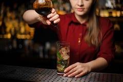 Weiblicher Barmixer, der einen Alkohol von der Flasche dem Cocktail hinzufügt Stockfotografie