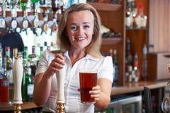 Weiblicher Barmixer Serving Beer Behind entgegengesetzt lizenzfreie stockfotografie