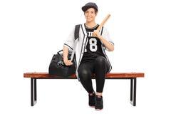 Weiblicher Baseball-Spieler, der auf einer Bank sitzt Stockfoto