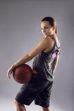 Weiblicher Basketball-Spieler, der für Kamera aufwirft Stockfotografie