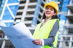 Weiblicher Bauingenieur, der die Entwürfe besichtigen Baustelle studiert Stockfotografie