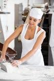Weiblicher Bäcker Holding Flour Scoop bei Tisch Lizenzfreie Stockfotografie