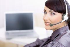 Weiblicher Bediener, der auf Kopfhörer spricht Lizenzfreies Stockbild