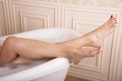 Weiblicher Beinfall über dem Badezimmer Stockbild