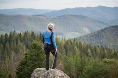 Weiblicher Bergsteiger auf der Spitze des Felsens mit kletternder Ausrüstung Lizenzfreie Stockfotografie