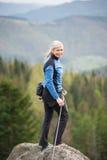 Weiblicher Bergsteiger auf der Spitze des Felsens mit kletternder Ausrüstung Stockfotografie