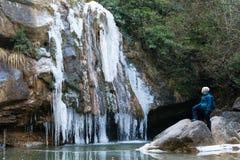 Weiblicher Bergsteiger, der den gefrorenen Winterwasserfall aufpasst Stockfoto