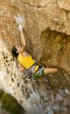 Weiblicher Bergsteiger, der einer Klippe anhaftet. Stockbilder