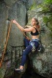 Weiblicher Bergsteiger, der mit Seil auf einer felsigen Wand klettert Stockbilder
