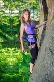 Weiblicher Bergsteiger, der mit Seil auf einer felsigen Wand klettert Stockfoto