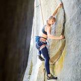 Weiblicher Bergsteiger, der mit Seil auf einer felsigen Wand klettert Lizenzfreies Stockbild