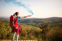 Weiblicher Bergsteiger, der der Wanderergruppe Rauchsignal schickt stockfotografie