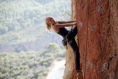 Weiblicher Bergsteiger, der zum nächsten Schritt prepearing ist Lizenzfreie Stockbilder