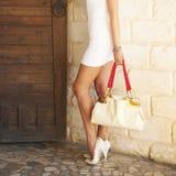Weiblicher beschuhter weißer hoher Absatz beschuht das Halten in einer Handmodetasche Stockfotografie