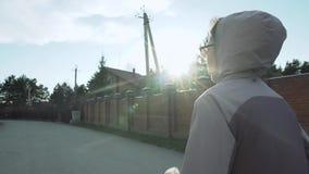 Weiblicher Betrieb in der kleinen Vorstadtstadt mit hohen Gebäuden im Hintergrund goldener Sonnenaufgang, slowmotion stock video