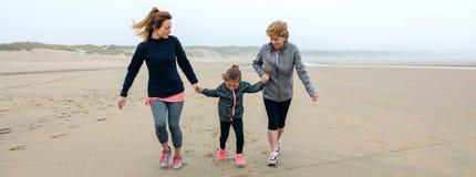 Weiblicher Betrieb von drei Generationen auf dem Strand stockbild