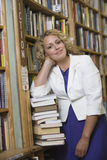 Weiblicher Bibliothekar Standing By Stack von Büchern Lizenzfreies Stockfoto
