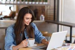 Weiblicher Blogger, der in einem Café stillsteht Stockfoto