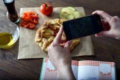 Weiblicher Blogger, der Fotos des gekochten Essens mit ihren Händen, Gemüsecracker, Blog kochend, Bullauge macht Lizenzfreies Stockbild