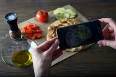 Weiblicher Blogger, der Fotos des gekochten Essens mit ihren Händen, Gemüsecracker, Blog kochend, Bullauge macht Stockbilder